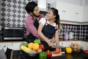 casal jovem feliz e sorridente cozinhando comida na cozinha de casa foto