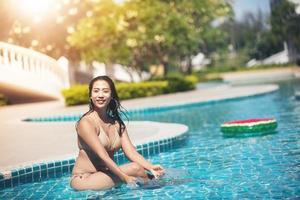 mulheres usam biquínis para nadar na piscina recreativa de verão foto