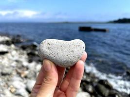 pedra de forma de coração na mão de meninas contra o fundo da praia. dia ensolarado de verão. conceito de amor, casamento e dia dos namorados. encontrar pedras bonitas e interessantes. férias na praia foto