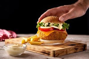 hambúrguer de frango crocante com queijo e batata frita foto