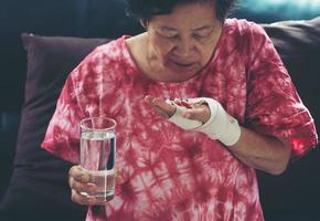 mulher asiática sênior tomando remédio pílula disponível foto