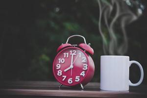 xícara de café e relógio branco na mesa de madeira com bokeh foto