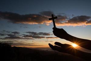 silhueta da mão segurando a cruz de Deus foto