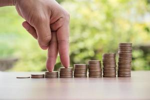 dedos subindo na pilha de moedas ou de dinheiro foto