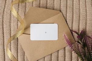 um cartão em branco é colocado em um envelope com uma fita, flores e um suéter. foto