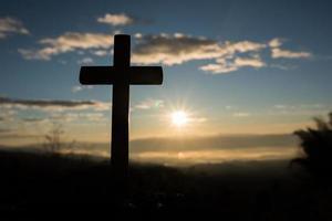 silhueta da cruz católica e do nascer do sol foto