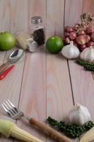 garfo, milho bebê, alho, pimenta fresca, limão e cebola roxa em um piso de madeira branco. foto