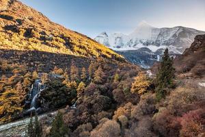 monte yangmaiyong com cachoeira na floresta de outono à noite. Yading Nature Reserve foto