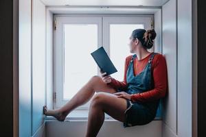 jovem sentada ao lado de uma janela lendo um livro durante um dia ensolarado, conceitos de reflexão e autocuidado, espaço de cópia foto