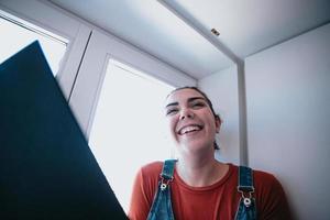 jovem sorrindo e rindo enquanto lê um livro na janela, dia claro, relaxamento e conceitos de saúde mental foto