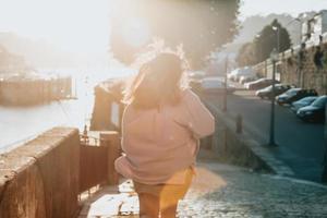 mulher fora de foco correndo durante um pôr do sol super vermelho na cidade, conceito de turismo foto