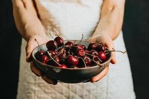velha garçonete oferece e segura um cacho de cereja em um prato, frutas, vida saudável, boa alimentação, conceitos mediterrâneos, cópia espaço, imagem vertical foto