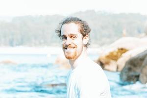 jovem hippie masculino com cabelo longo cacheado e barba sorrindo para a câmera durante um dia ensolarado na praia, felicidade e relaxamento conceitos foto