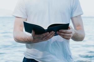 close-up de um homem segurando um livro durante a leitura, conceitos religiosos e de estudo, praia e dia claro foto