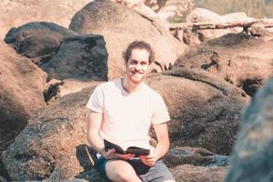 jovem hippie sorrindo para a câmera em uma camisa branca lendo um livro na rocha da praia durante um dia de verão, férias relaxantes e liberdade foto
