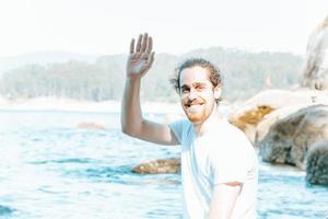 jovem hippie masculino com cabelo longo cacheado e barba sorrindo e saudando a câmera durante um dia ensolarado na praia, felicidade e relaxar conceitos foto