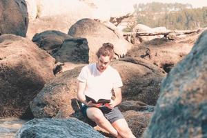 jovem hippie de camisa branca lendo um livro na rocha da praia durante um dia de verão, férias relaxantes e liberdade foto