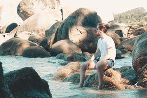 jovem solitário na praia sentado nas rochas, olhando para longe da câmera durante um dia de praia, conceito de reflexão e suspense, espaço de cópia foto