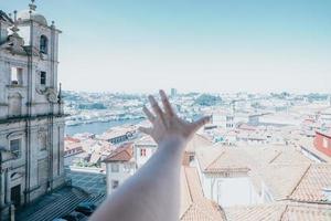 uma mão sobre a cidade do porto num dia superluzente, viajar e visitar o conceito de turismo de cidade foto