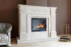 lareira em mármore branco em estilo clássico com lenha no interior. foto