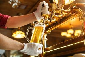 mãos de barman servindo cerveja light em um copo foto