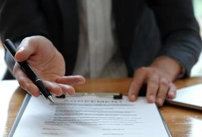 empresários vendendo a casa apontando para a assinatura do contrato de venda no escritório. foto