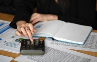 mulher faz cálculos em uma calculadora no escritório com a folha de dados colocada na mesa. foto