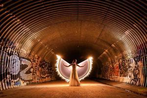 posando com a luz de uma mulher pintada com asas em um túnel de esgoto foto