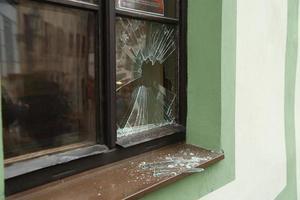 janela quebrada da rua e cacos de vidro foto
