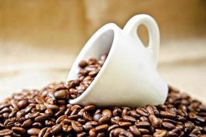xícara de café e grãos de café torrados foto