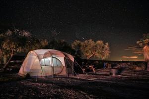 barraca acampada à noite sob as estrelas e a Via Láctea foto