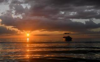 silhueta de barcos de pesca na hora do sol. foto