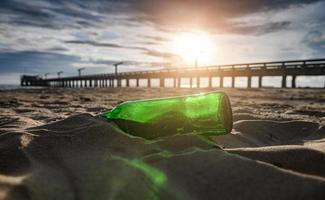 resíduos de garrafa de vidro verde na praia. foto