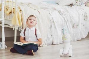 menino bonito vai para a escola pela primeira vez. criança com mochila escolar e livro. criança faz uma pasta, quarto de criança em um fundo. de volta à escola foto