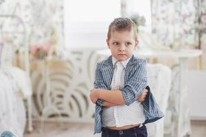conceito de educação, infância, pessoas, lição de casa e escola. menino triste em jaqueta de escola foto