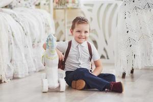 menino com uma mochila se senta na sala das crianças e brinca com brinquedos. pela primeira vez na escola. Infância feliz foto