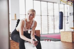 foto de uma mulher atraente fitness na academia segurando uma garrafa de água