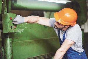 trabalhador industrial trabalhando com torno na indústria metalúrgica foto
