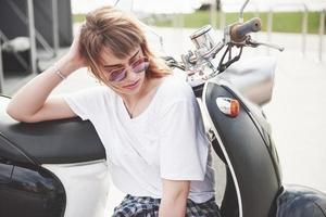 retrato de um hipster linda garota sentada em uma scooter retrô preta, sorrindo, posando e desfrutar do sol quente de primavera. foto