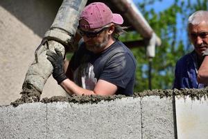 uma combinação de trabalho manual por um pedreiro e uma bomba de concreto durante a colocação de concreto nas paredes foto