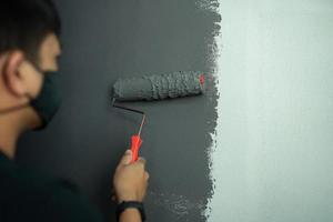 jovem pintando uma parede interior de cor escura com um trabalho conceitual de casa foto