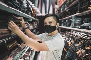 jovem comprando na loja de roupas da moda com um novo estilo de vida normal usando máscara foto