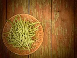 feijão verde vegetal em fundo de madeira foto