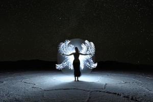 luz pintada imagem de longa exposição de uma mulher com a Via Láctea foto
