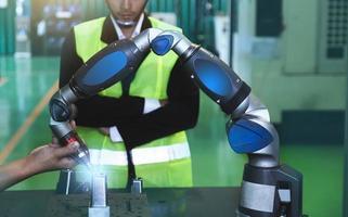 engenheiros asiáticos masculino feminino em uso industrial capacetes na indústria manufatura fábrica exibição mecânica braço de interface robô manufatura tecnologia engenheiro foto