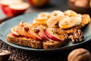 torradas com manteiga de amendoim, maçã, banana, nozes e mel. conceito de pequeno-almoço vegetariano saudável. foto