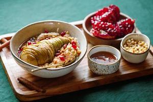 aveia durante a noite com canela, mel, pêra, sementes de romã e pinhões. pequeno-almoço vegano saudável. foto