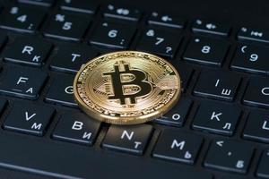 Moeda metálica de bitcoin sobre teclado preto de letras de computador, close-up foto