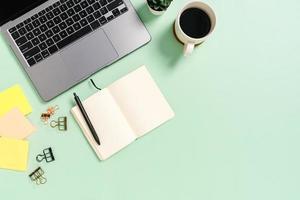 foto plana leiga criativa da mesa do espaço de trabalho. mesa de escritório de vista superior com laptop, xícara de café e caderno preto de maquete aberta sobre fundo de cor verde pastel. vista superior simulada com fotografia do espaço da cópia.