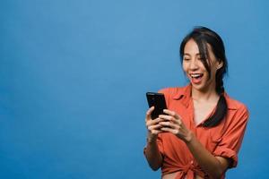 jovem asiática usando telefone com expressão positiva, sorri amplamente, vestida com roupas casuais, sentindo felicidade e carrinho isolado sobre fundo azul. feliz adorável feliz mulher alegra sucesso. foto